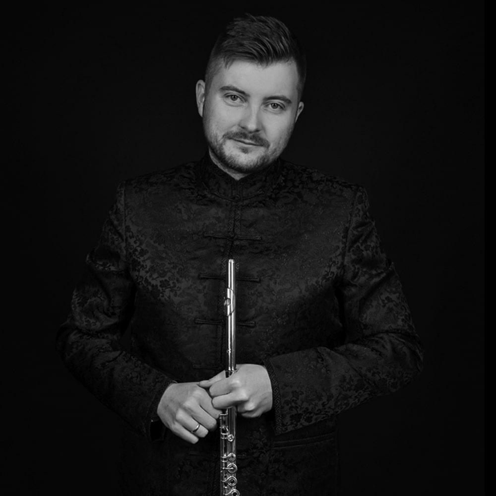 Fotografia: Lukasz Długosz, muzyk – mężczyzna w stroju scenicznym trzymający flet poprzeczny