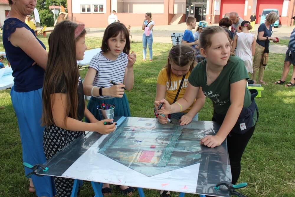 fotografia: cztery dziewczynki malują na planszy rozłożonej na stole Karawana Wędrujący Festiwal Sztuki i Animacji