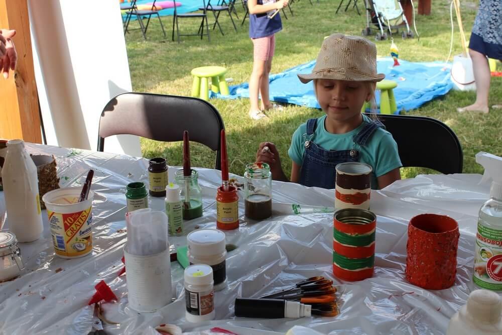 fotografia: dziewczynka siedzi przy stoliku z farbami Karawana Wędrujący Festiwal Sztuki i Animacji