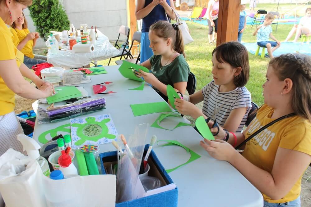 fotografia: trzy dziewczynki siedzą przy stoliku i wycinają kolorowy papier Karawana Wędrujący Festiwal Sztuki i Animacji