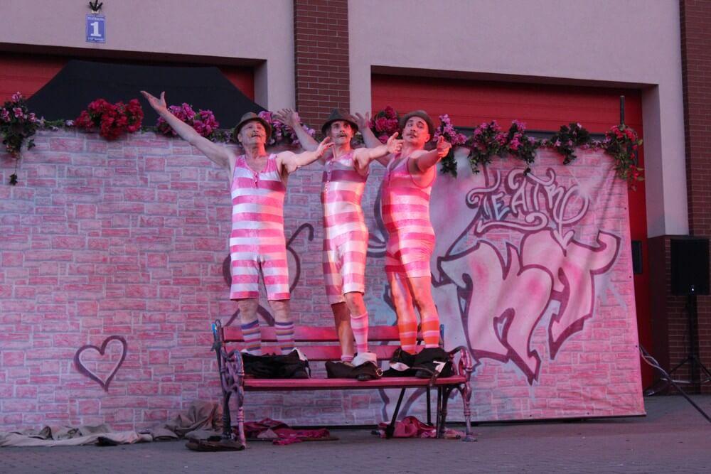 fotografia: trzech aktorów teatru akt w pasiastych kostiumach stoi na ławce Karawana Wędrujący Festiwal Sztuki i Animacji