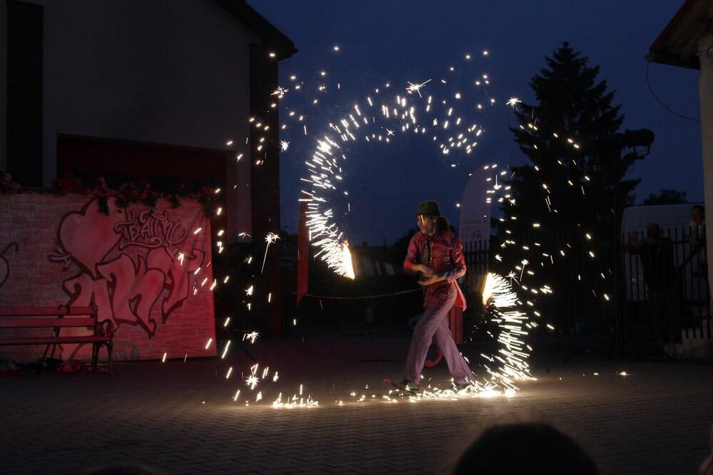 fotografia: aktor teatru akt w ciemnościach używa efektów pirotechnicznych Karawana Wędrujący Festiwal Sztuki i Animacji