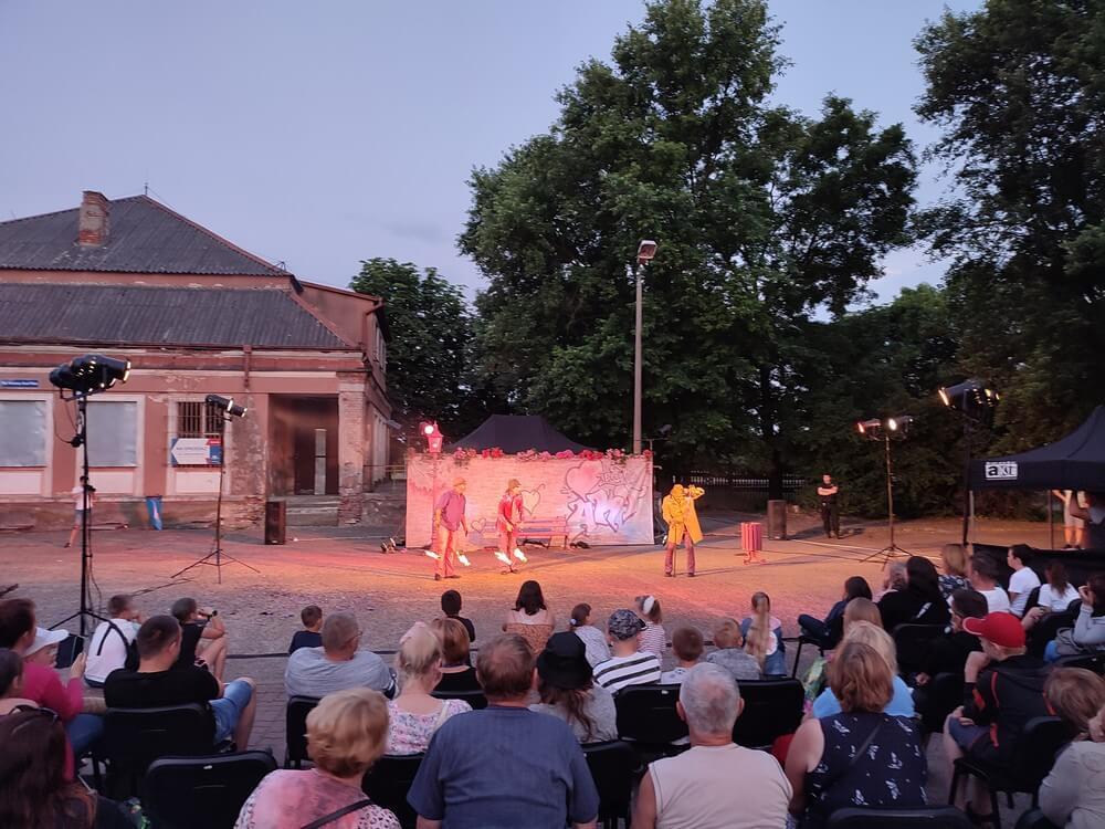 fotografia: publiczność oglądająca spektaklu teatru akt na placu, w tle budynek. Karawana Wędrujący Festiwal Sztuki i Animacji