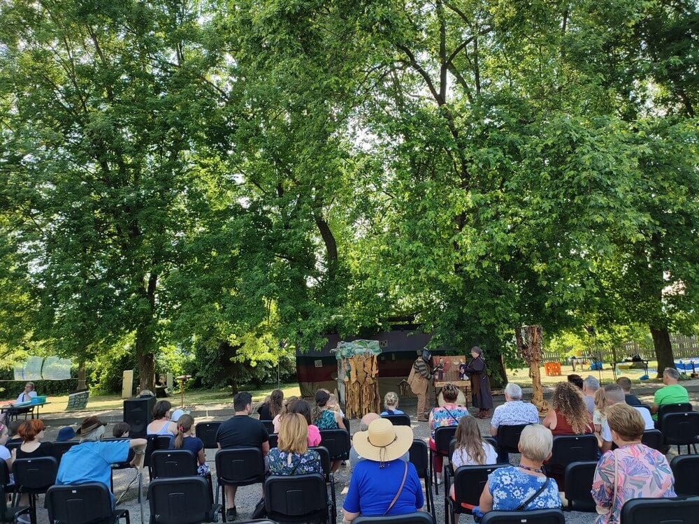 fotografia: publiczność oglądające spektakl plenerowy w parku Karawana Wędrujący Festiwal Sztuki i Animacji
