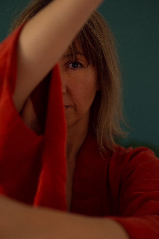 fotografia: zbliżenie twarzy kobiety, twarz częściowo zasłonięta uniesionym ramieniem