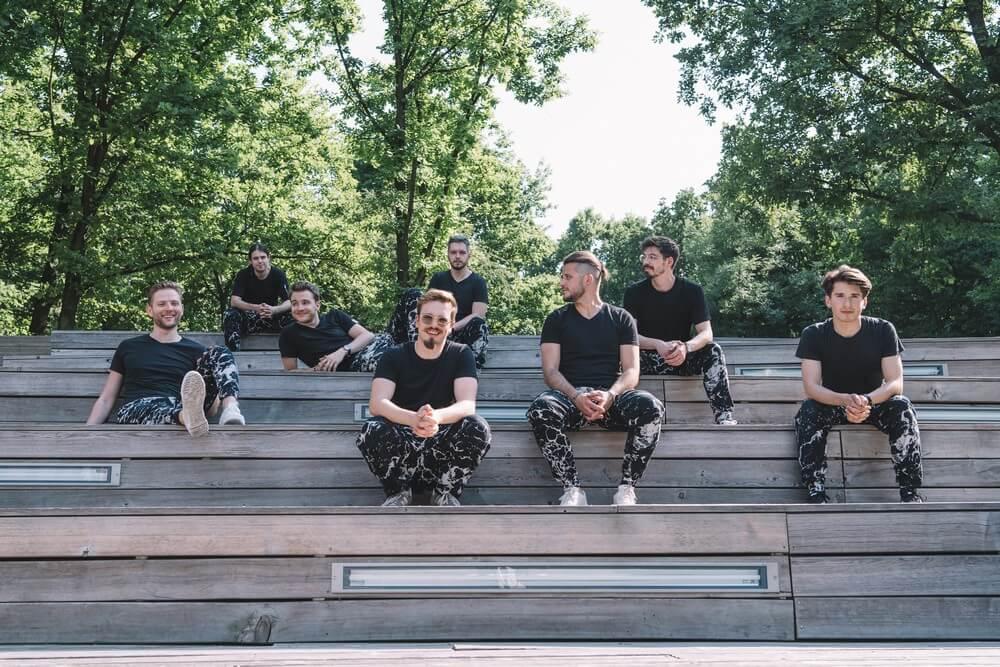 fotografia: muzycy - ośmiu uśmiechniętych młodych mężczyzn, siedzących w rozproszeniu na drewnianych schodach, ubranych w czarne t-shirty oraz czarno-białe spodnie typu marmurki