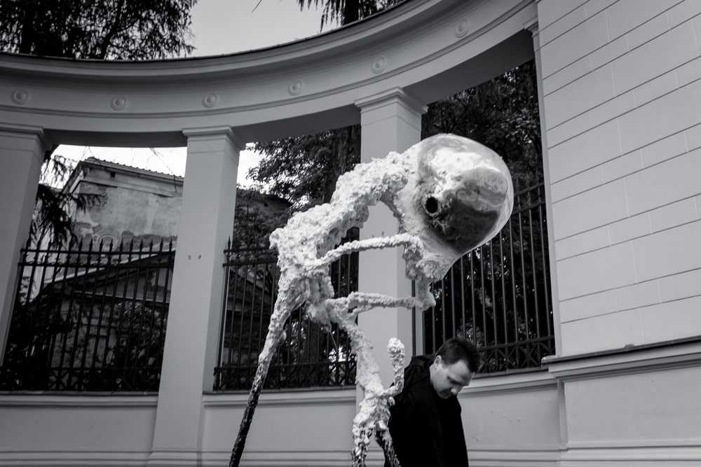 fotografia: na tle kolumnady rzeźba abstrakcyjna, obok autor Jan Gostyński