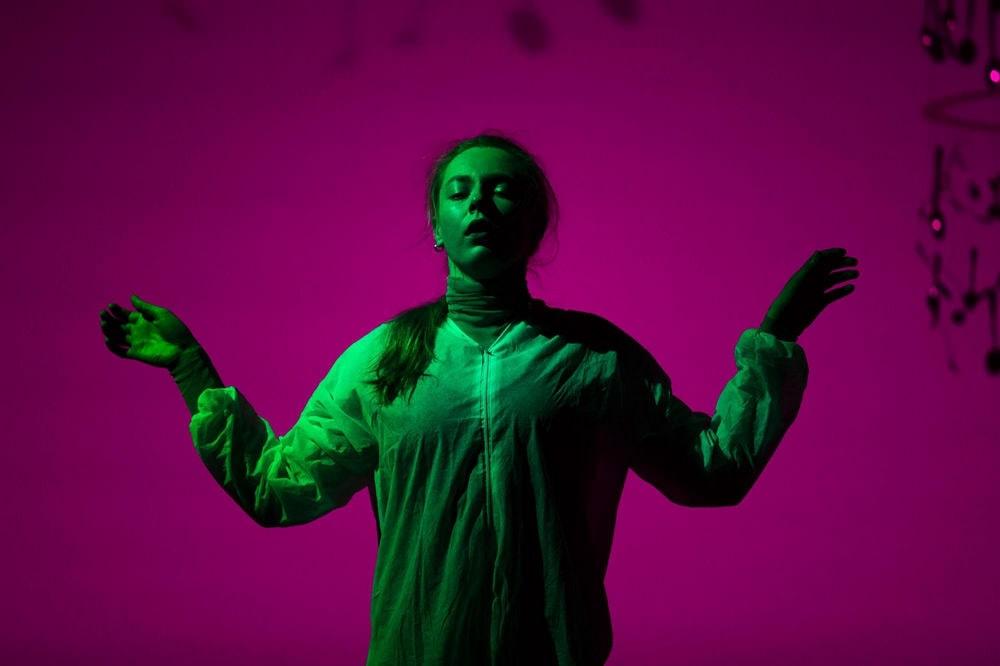fotografia: na fioletowym tle stoi kobieta z rozłożonymi rękami, oświetlona na zielono