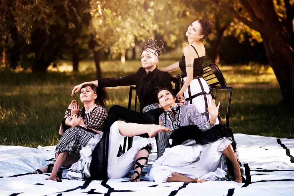 fotografia: pięcioro aktorów mimów na tle drzew - stoją i siedzą