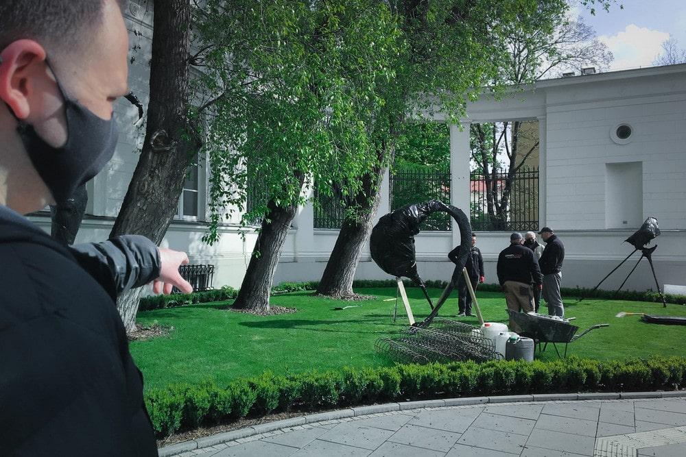 fotografia: grupa osób przy montażu rzeźby na trawniku