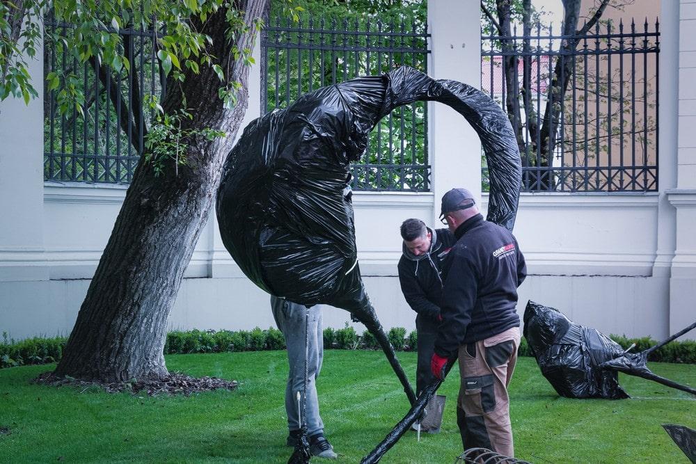fotografia: dwie osoby przy montażu rzeźby zawiniętej w czarną folie ochronną. na trawniku przed mik