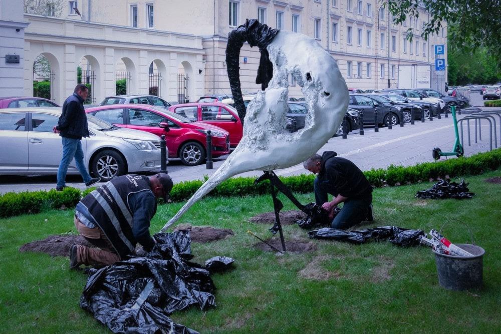 fotografia: montaż rzeźby abstrakcyjnej na trawniku przed budynkiem MIK, dwie osoby pracują przy montażu