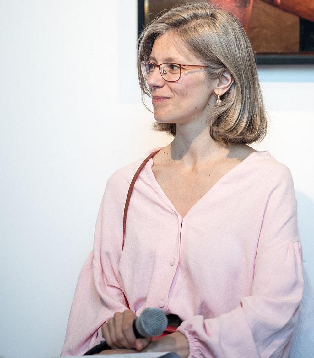 fotografia: Agnieszka Wolny-Hamkało, portret, kobieta w jasnej bluzce, w okularach, jasne włosy, trzyma w ręku mikrofon