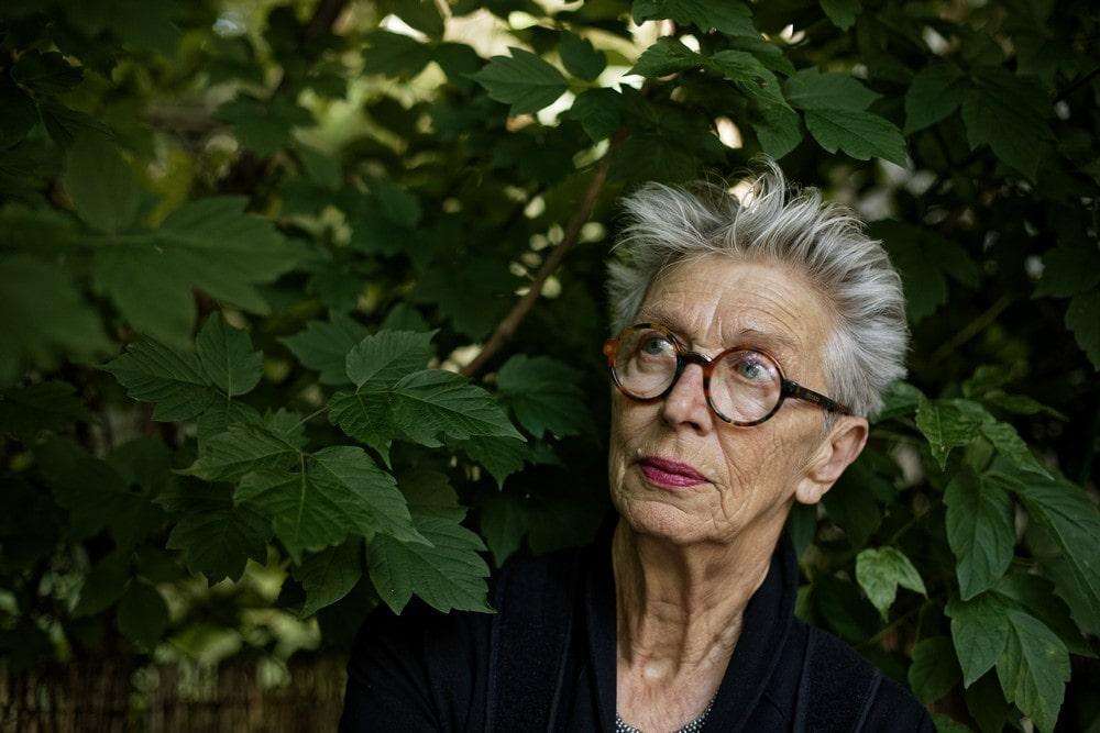 fotografia: Anda Rotenberg, portret kobiety w okularach, z krótkimi siwymi włosami, na tle roślinności