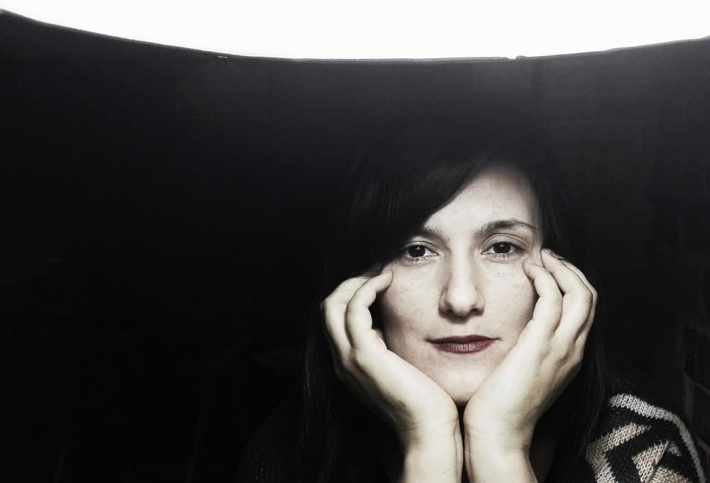fotografia: Bianka Rolando, portret, zbliżenie na twarz, kobieta opiera brodę na podstawie dłoni, palce opiera na twarzy, ciemne tło
