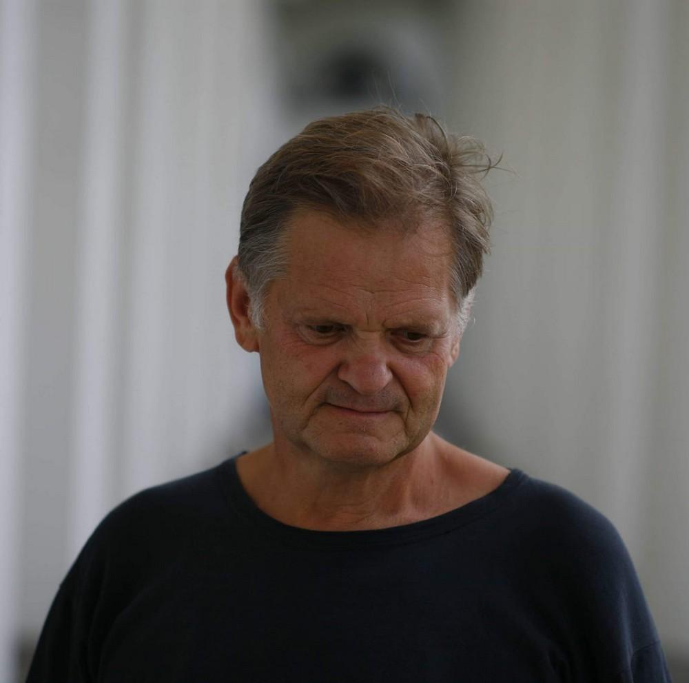 fotografia: Jarosław Mikołajewski, portret, mężczyzna w ciemnym swetrze patrzy w dół