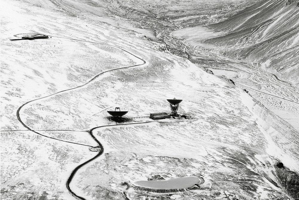 fotografia czarno-biała: na szarym tle dwie anteny paraboliczne, widok z góry