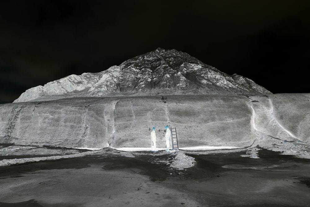fotografia czarno biała, negatyw: na tle wzgórza dwie postacie ludzkie