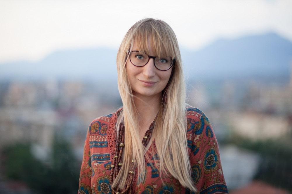 fotografia: Małgorzata Rejmer, portret, jasnowłosa kobieta w okularach ubrana w barwną bluzkę