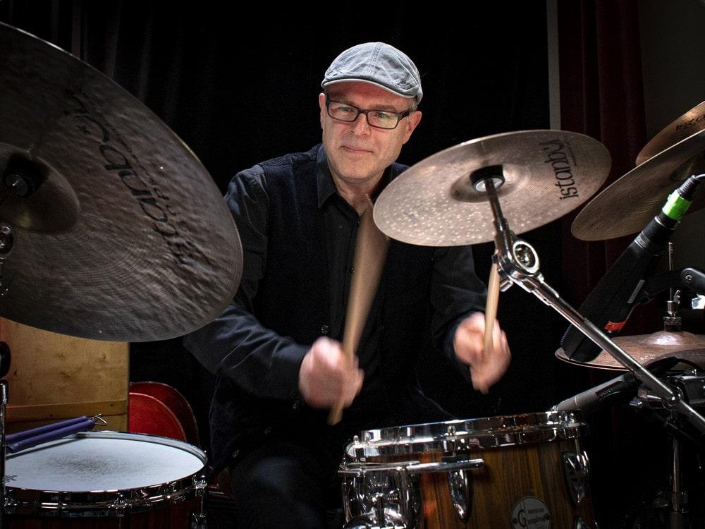 fotografia marcina jahra: uśmiechnięty mężczyzna w okularach, w koszuli i kamizelce koloru czarnego, grający na perkusji, trzyma w dłoniach pałki perkusyjne