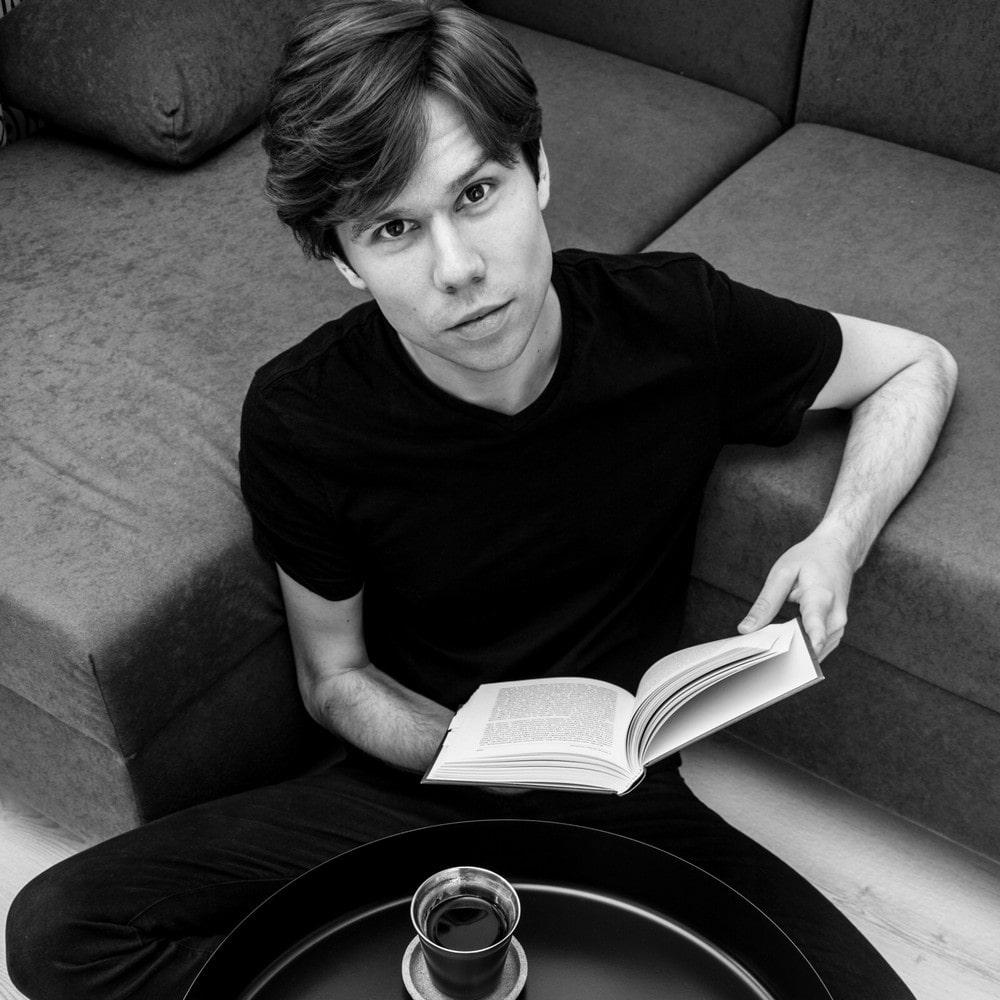 fotografia czarno-biała: Mateusz Adamczyk, zdjęcie wykonane z góry, mężczyzna trzyma w ręku otwartą książkę