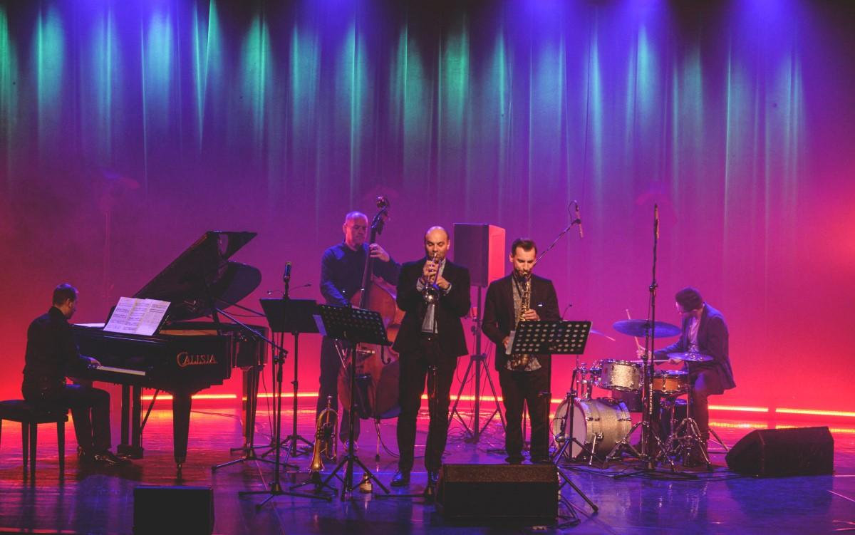 fotografia: pięciu muzyków na scenie, grają na instrumentach, tło podświetlone na czerwono