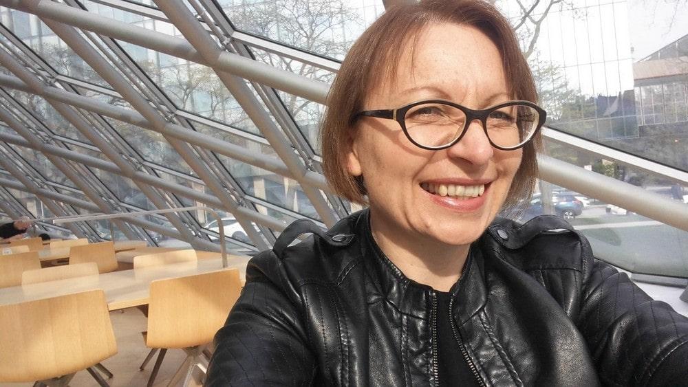 fotografia: Renata Ziemińska, zbliżenie twarzy, kobieta w okularach ubrana w czarną kurtkę, w tle przeszklona ściana i stoły z krzesłami