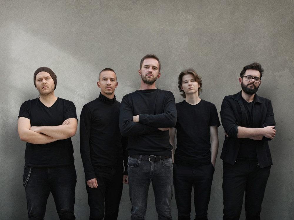 fotografia: pięciu mężczyzn. ubrani na ciemno, stoją obok siebie, patrzą się w obiektyw