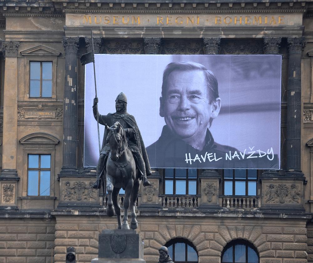 fotografia: baner z portretem Vaclava Havla zawieszony na budynku, na pierwszym planie rzeźba zbrojnego mężczyzny na koniu