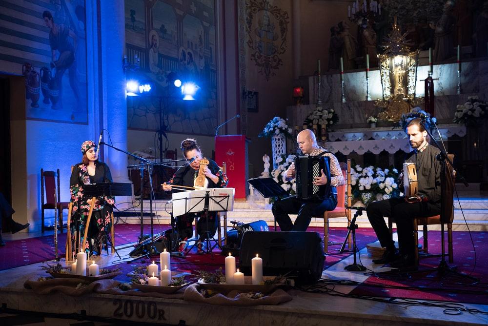 Zespół Marii Pomianowskie, czworo muzyków, gra w kościele, w tle ołtarz