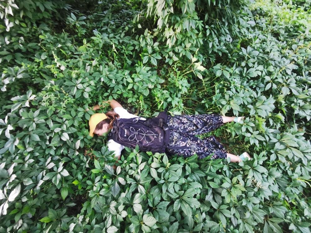 fotografia: sylwetka ludzka z plecakiem, leżąca twarzą do ziemi wśród roślin