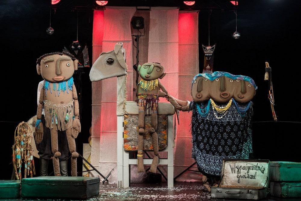 fotografia: scena z przedstawienia teatru lalkowego. stoja lalki przedstawiające w uproszczeniu ludzkie postacie. W środku jedna siedzi na figurze podobnej do konia