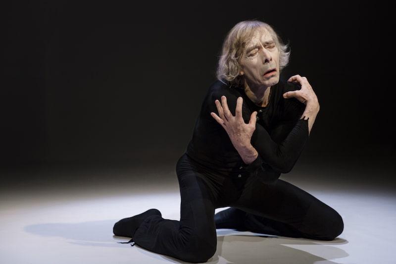 fotografia: aktor mim klęczy, wyraz cierpienia na twarzy