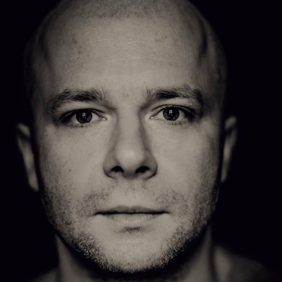 fotografia czarno biała: zbliżenie na twarz mężczyzny na ciemnym tle