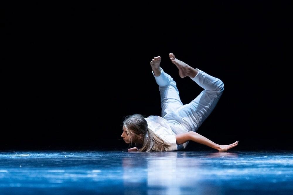 fotografia: kobieta na scenie, w białym kostiumie leży na podłodze