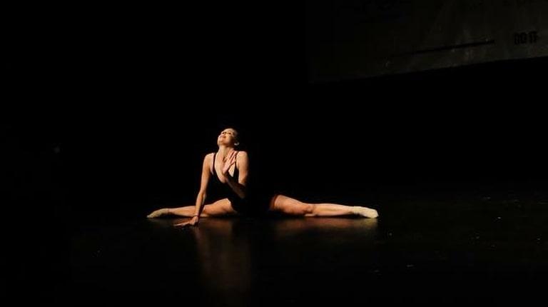 fotografia: kobieta na ciemnym tle, siedzi na scenie w szpagacie bocznym