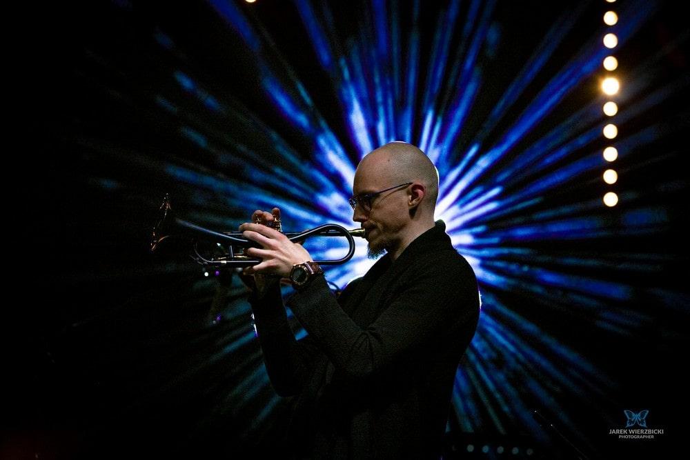 fotografia: piotr Schmidt z boku grający na trąbce, na ciemny tle widoczne jasne promienie światła