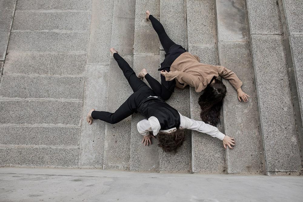 fotografia: dwie osoby leżące na schodach sfotografowane z góry