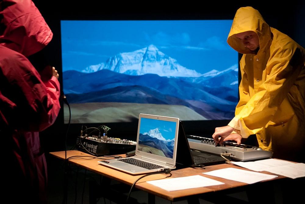 fotografia: dwie osoby w ubraniach przeciwdeszczowych z kapturami, stoją przy komputerze i instrumencie klawiszowym, w tle obraz góry i pofalowanego morza