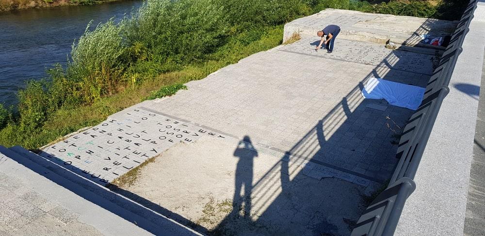 fotografia: dwie osoby rysują litery na dużej betonowej płycie